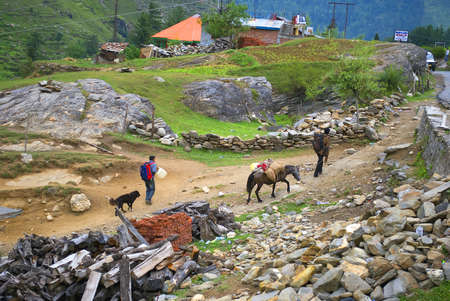 A porter and his donkey leads a trekker through hilly village way. A dog follows them. Editorial