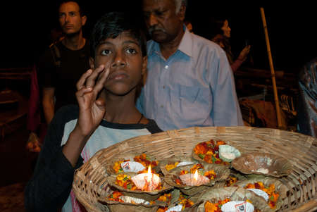 A young Indian boy is selling a basket full of floral candles to float as offerings on the River Ganges in Varanasi in the Uttar Pradesh region of India. Varanasi, one of worlds oldest living cities, is rightly called the religious capital of India.