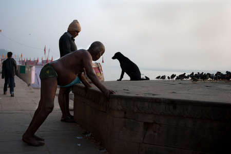 rid: An Indian man is doing physical exercise in the early morning on the river bank at Varanasi, India. Many people engage themselves in morning walk and exercise to get rid of obesity.