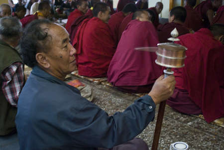 dalai: A Buddhist man is moving a prayer wheel with a group of Buddhist monk is doing prayer at the Monastery of Dalai Lama in Dharamshala, Himachal Pradesh, India Editorial