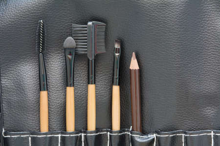 leatherette: top view of professional makeup brush on black leatherette background