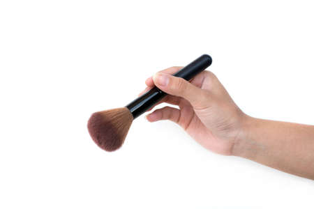 brush in: isolated professional makeup brush in womens hand