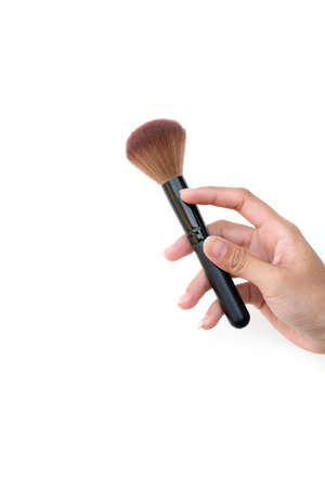 women's hand: isolated professional makeup brush in womens hand