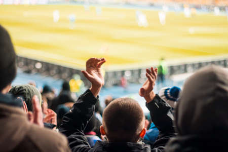 Silhouettes of hands and the fans in the stadium Stock Photo