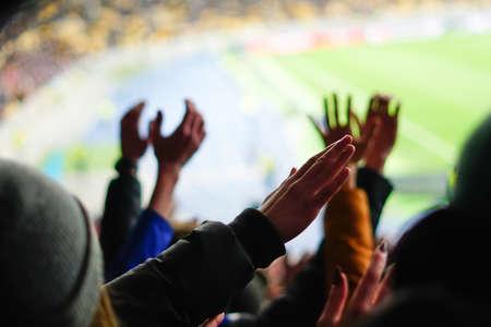 Fußballfans heben die Hände, singen, unterstützen die Nationalmannschaft im Stadion