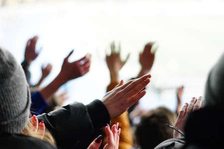 Aficionados al fútbol levantando manos, cantando, apoyando a la selección nacional en el estadio Foto de archivo