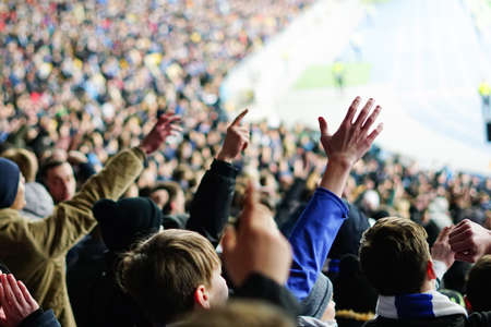 Football fans clapping on the podium of the stadium Imagens