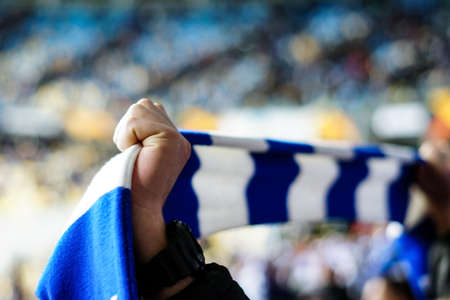 Overjoyed football fan holding a scarf and cheering Imagens