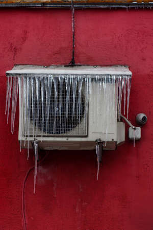 The conditioner covered with icicles on a yellow wall Stockfoto