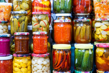 Jars of pickled vegetables and fruits in the garden. Marinated food. Stockfoto