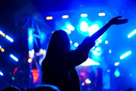 Chica en hombros entre la multitud en un festival de música.