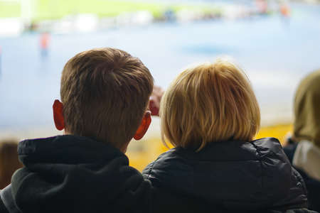 Fans in the autumn watching football at the stadium