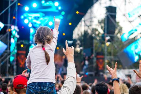 Children sit around the neck at a street concert