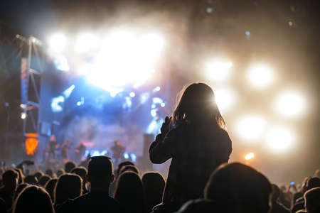 Child has fun on her parents' shoulders keeping hands with them at an outdoor rock music concert Stock Photo