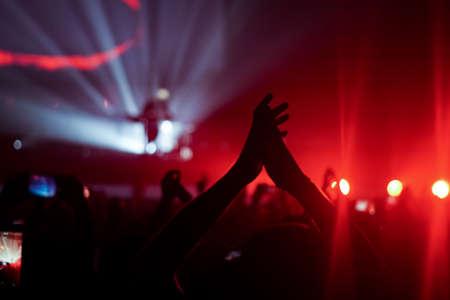 sagome di folla di concerti davanti a luminose luci del palcoscenico Archivio Fotografico