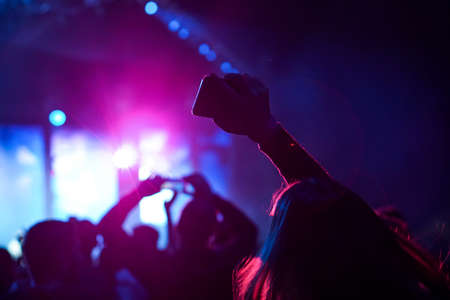 Audience with hands raised at a music festival and lights streaming down from above the stage. Soft focus, high ISO, grainy image. Archivio Fotografico - 134733606