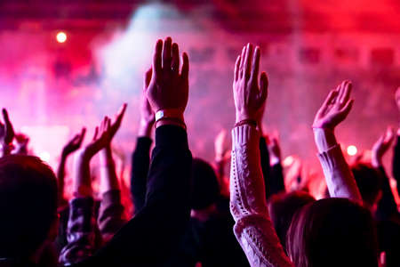 Audience with hands raised at a music festival and lights streaming down from above the stage. Soft focus, high ISO, grainy image. Archivio Fotografico - 134733614