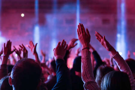 Audience with hands raised at a music festival and lights streaming down from above the stage. Soft focus, high ISO, grainy image. Archivio Fotografico - 134733621