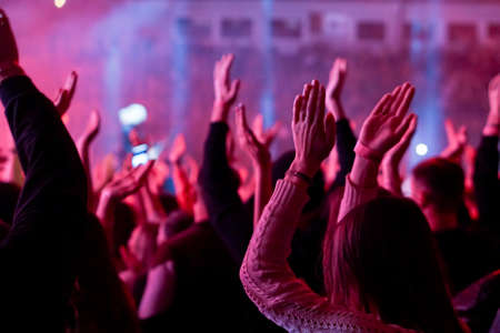 Audience with hands raised at a music festival and lights streaming down from above the stage. Soft focus, high ISO, grainy image. Archivio Fotografico - 134733623