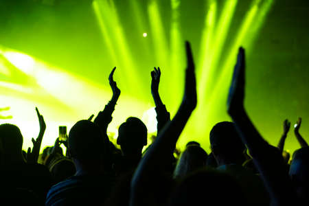 Audience with hands raised at a music festival and lights streaming down from above the stage. Soft focus, high ISO, grainy image. Archivio Fotografico - 134733636