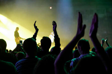 Audience with hands raised at a music festival and lights streaming down from above the stage. Soft focus, high ISO, grainy image. Archivio Fotografico - 134733638