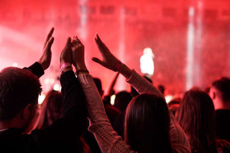 Audience with hands raised at a music festival and lights streaming down from above the stage. Soft focus, high ISO, grainy image. Archivio Fotografico - 134768407