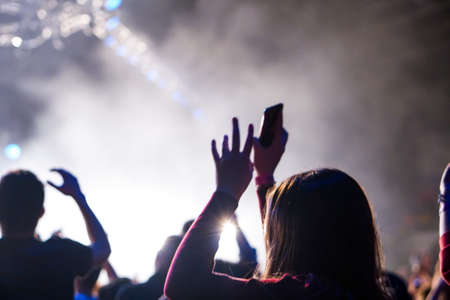 Audience with hands raised at a music festival and lights streaming down from above the stage. Soft focus, high ISO, grainy image. Archivio Fotografico - 134768612