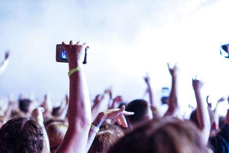 Folla a un concerto di musica, pubblico che alza le mani