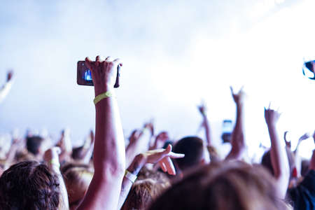 Tłum na koncercie muzycznym, publiczność podnosząca ręce do góry