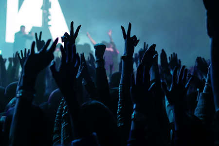 Audience with hands raised at a music festival and lights streaming down from above the stage. Soft focus, high ISO, grainy image. Zdjęcie Seryjne