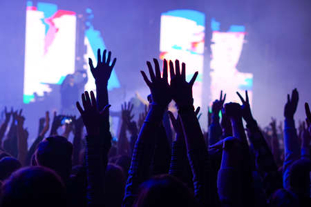 Audience with hands raised at a music festival and lights streaming down from above the stage. Soft focus, high ISO, grainy image. Archivio Fotografico - 134733981