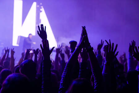Audience with hands raised at a music festival and lights streaming down from above the stage. Soft focus, high ISO, grainy image. Archivio Fotografico - 134733984