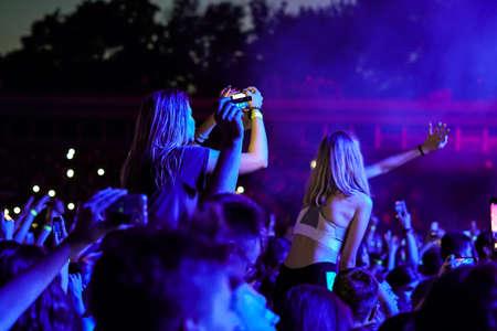 Crowd at a music concert, audience raising hands up Zdjęcie Seryjne