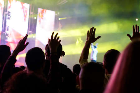 Audience with hands raised at a music festival and lights streaming down from above the stage. Soft focus, high ISO, grainy image. Archivio Fotografico - 134769343