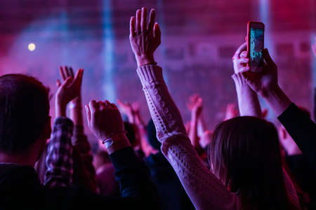 Audience with hands raised at a music festival and lights streaming down from above the stage. Soft focus, high ISO, grainy image. Archivio Fotografico - 134769462