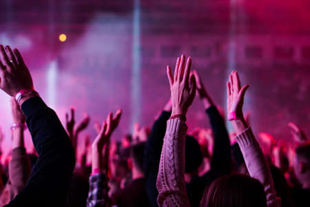 Audience with hands raised at a music festival and lights streaming down from above the stage. Soft focus, high ISO, grainy image. Archivio Fotografico - 134769463