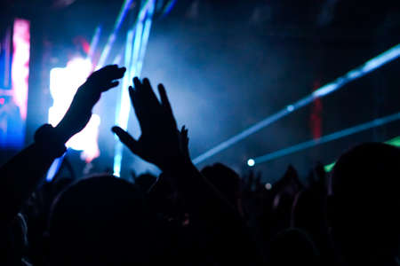Audience with hands raised at a music festival and lights streaming down from above the stage. Soft focus, high ISO, grainy image. Archivio Fotografico - 134769552