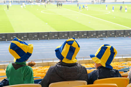 children watching while enjoying a game from seats for spectators in the stadium Banque d'images