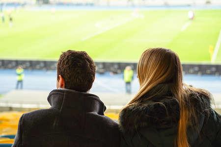 spectators watch football in a half-empty stadium