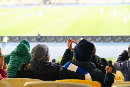 children watching while enjoying a game from seats for spectators in the stadium