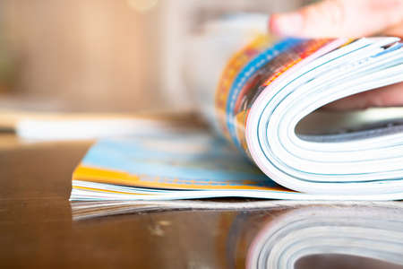 Closeup background of a pile of old magazines with bending pages