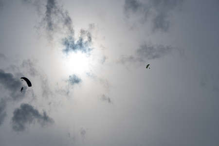 Silhouette of a parachutist in flight before sunset