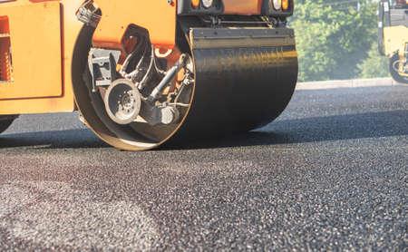 steamroller compact flatten out the asphalt tar