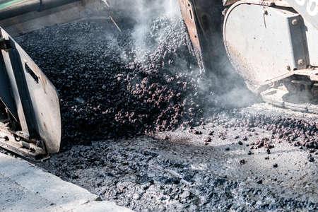 Industrial pavement machine laying fresh asphalt on highway