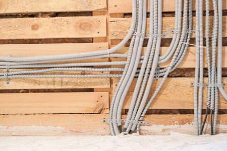 Aluminum tubing for wire protection lined up on old concrete wall.