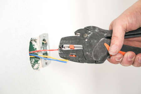 Electrician, monitors the wires in the sockets. Close up with tools