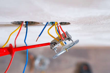 Hands of electrician installing socket in gypsum wall