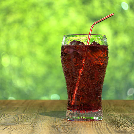 Very high resolution 3d rendering of a glass of fresh iced cola on a wood table