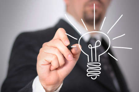 Businessman sketching a light bulb on a glass Stock Photo