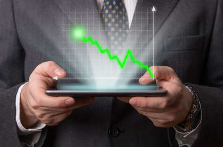 holography: Businessman using a futuristic tablet with an holography diagram Stock Photo